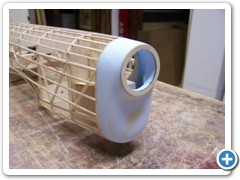 tack the blue foam nose block to the front fuselage former, then carve and sand to shape.